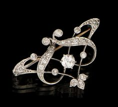 Unmarked white gold brooch in Art Nouveau design, set with round cut diamonds.