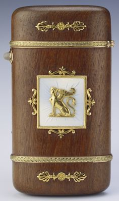 Fabergé cigarette case, tall rounded rectangular of palisander wood, square central mounts of radiating guilloché oyster enamel with gold beaded frame and seated sphinx, two red and green gold foliate bands circle the case, four gold anthemions placed at the ends of the case, moonstone thumbpiece. Michael Perchin, 1903. Acquired by Prince Henry, The Duke of Gloucester; by whom given to King George V.