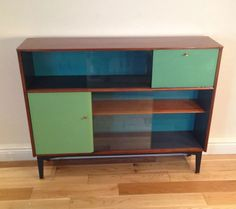 This true Vintage Nathan Teak display cabinet with glass doors is a gem! Refurbished and upcycled to a high standard, this sideboard could be the focal point in any room! The colour used are three shades of green, including a stylish peacock for the back. This fifty's sideboard/display has been given new life!