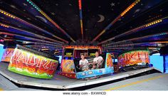 Two young men on the Waltzers, one of the fairground rides on Brighton Pier - Stock Image