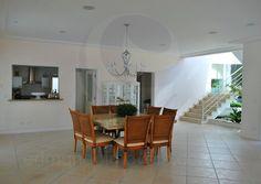 Cruzando a porta de entrada, o salão principal conecta quatro ambientes: o hall de entrada, o living room, a sala de jantar (que acomoda até oito convidados) e a cozinha, que possui um balcão estilo americano, facilitando o serviço das refeições indoor.