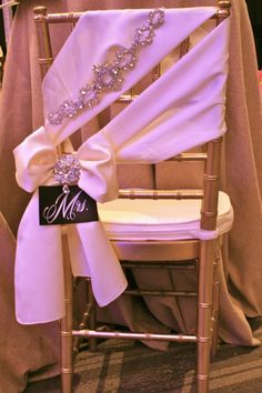 "Gold chivari bridal chair with ivory satin sash, Swarovski crystal jewelry accents, and ""Mrs."" placard 