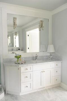 Sophisticated bathroom features a white vanity fitted with an angled cabinet to make room for a corner shower topped with gray marble under an inset mirror lined with polished nickel sconces.