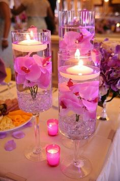 Pink tabel decoration. Vases with flowers and candles