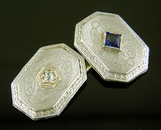 Beautifully engraved platinum-top cufflinks set with striking blue sapphires and sparkling white diamonds. The borders are decorated with intricate geometric and floral designs in the best Art Deco taste. An elegant accent to any cuff. Created in platinum and 14kt gold, circa 1920. http://www.jewelryexpert.com/catalog/Sapphire-and-Diamond-Cufflinks-J9399.htm