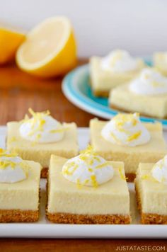 Easy Lemon Cheesecake Bars on white plate with cut lemon and more bars on a blue plate in background.