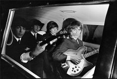 The Beatles stare out from inside a limo. Bet they lost count how many they'd been inside!