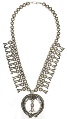 "A Navajo squash blossom necklace  Stamped ""United Indian Traders Association 12 "", the heavy silver necklace hung with two dozen blossoms and a particularly elaborate naja.  length 17in"