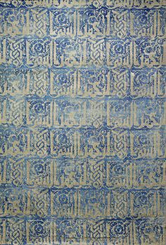 Fortuny woven silk Panel with kufic decoration, Venice, circa 1920 rectangular, blue stamped with applied silver, depicting rows of kufic inscription on a scrolling arabesque background, mounted 86.5 x 58.5 cm.
