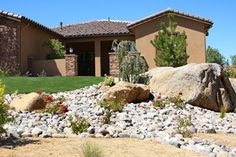 Boulders and rocks at the corner of driveway..Add succulents for full sun