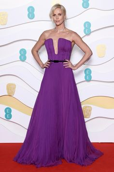 At the BAFTAs 2020 Charlize Theron wore her boldest Dior dress yet. Vogue speaks to Charlize Theron's stylist, Leslie Fremar, to get all the details on her BAFTAs 2020 dress. Charlize Theron, Kate Middleton, Magenta, Bright Purple, Sandy Powell, The Baftas, Alexander Mcqueen, Purple Gowns, Purple Dress