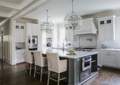 Stunning kitchen with white cabinets, gray island painted in Benjamin Moore's Iron Mountain, pendant lighting, farmhouse sink, marble countertops and white subway tile backsplash | JackBilt Homes