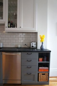 Gray cabinets against white subway tile and hardwood floors.  Also glass cabinet door! Good kitchen inspiration.