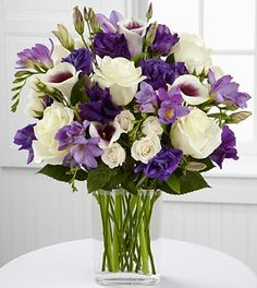 Bi-colored purple and white Picasso Calla Lilies are simply fascinating seated amongst deep purple lisianthus, lavender freesia, white roses, cream spray roses and lush greens.