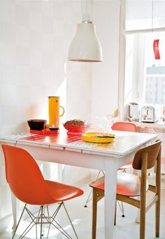 Cute small dining area, orange chairs, white.