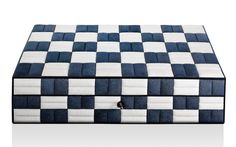 A checkerboard pattern turned out in textured and tufted navy and white shagreen adorns a cedar box containing compartments and a leather writing pad. A stylish hold-all for a vanity or desk.