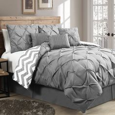 Instantly beautify your bedding game with this eye-catching comforter set, an alluring addition to any restful retreat. Woven of polyester and stuffed with a plush poly fill, this set offers up a pinched pleat design on top and a complementing chevron print on the other side for a pop of pattern. Along with its classic comforter, this set also includes two shams, three decorative pillows, and a bed skirt to complete your ensemble. Just let it outfit your bed for a marvelous master suite in…