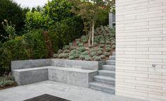 Terrassenanlage mit Naturstein Sitzbank als Stützmauer