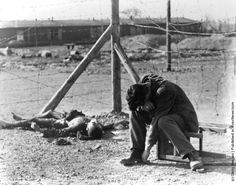 A Polish prisoner at Erla concentration camp near Magdeburg in Germany, beside the corpse of a fellow prisoner who was burnt by the Germans. (Photo by Margaret Bourke White/Getty Images). 05-1945