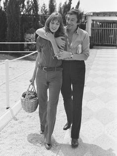 Jane Birkin wears a t-shirt, belted pants, square-toe boots, layered necklaces, and her signature basket