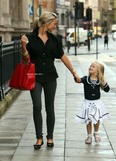 Alex Curran Gerrard (with one of her adorable daughters) in black skinny jeans, black Alexander McQueen shirt, and black Miu Miu flats, accessorized with bright red Fendi bag.