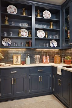 We ♥️ the dark navy bar from Bunny Williams' 2015 idea house. Her gold pineapple trios work so well with the brass hardware and moody paint color! Psst- the paint color is Sherwin Williams Inkwell #SW6992