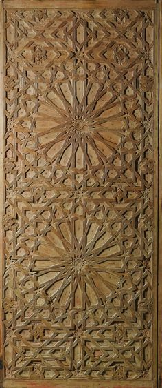 A RARE CARVED WOOD DOOR PANEL, SPAIN OR MOROCCO, LATE 15TH- 16TH CENTURY of rectangular form, comprising of pinewood sections decorated with an intricate geometric pattern composed of two large sixteen-pointed stars, interstices filled with smaller stars and polygons, reverse side decorated with one half of a monumental shamsa with geometric rays radiating further smaller half shamsas, with further interlocking polygons and stars, traces of colour pigment, mounted on iron display stand