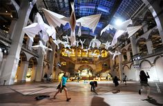 sipho mabona flocks gigantic origami birds in tropenmuseum's great hall