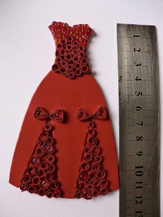 Miniature paper dress with quilled decorations. I cannot imagine all the different ways to decorate this with seed beads.
