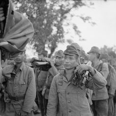 Japanese troops of the 52nd Division hand over their weapons to the 1/10th Gurkha Rifles (17th Indian Division) after surrendering at a railway bridge over the Sittang River in Burma.