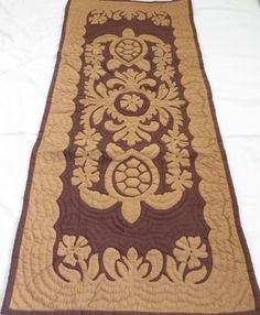 Hawaiian quilt table runner 100% hand quilted/hand appliqued Hawaiiana by Hawaiian Quilt Shop. $59.95. 100% Hand Quilted and 100% Hand Appliqued. There's a count of 6-8 stitches in an inch. Turtle (Honu) Design. 100% Brand New Hawaiian Handmade Table Runner / Wall Hanging 20x50. It has 3 loops in the back where you can insert a rod for easy hanging. ALOHA, this quilt is made of 65% Polyester and 35% Cotton.  Which makes the quilt 100% machine washable.  We hand-washed all...