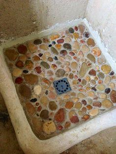 Así está quedando el suelo de la ducha. Con piedras recogidas del río por nosotros mismos. Me encanta!!
