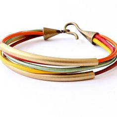 Leather and Tube Bangle Wrap Bracelet The Five color leather cord bracelet is connected with an antique brass hook and eye closure and had two golden brass tubes. The leather cord colors are: Orange,