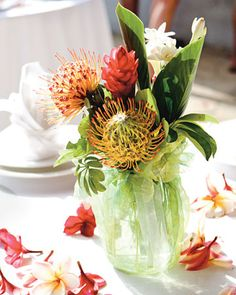 Mason jar centerpieces wrapped in sheer fabric hold pincushion protea, red ginger, and white tuberose
