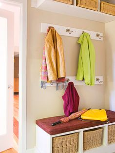 You don't need a lot of space to set up a simple mudroom. This small but efficient space features hooks, baskets, and shelves that keep clutter organized and out of sight. A cushy bench serves as a perch for people to sit while taking off shoes.