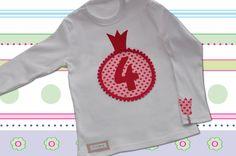 Süßes graues Geburtstagsshirt für Mädchen. Im gepunkteten Kreis befindet sich eine pinkfarbene Geburtstagszahl - alles liebevoll appliziert und mit weißem Pomponband verziert. Das Ärmelchen ziert...