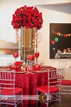 Centro de mesa con flores rojas sobre jarrón rectangular de espejos. #CentroDeMesa