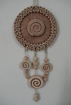Závěs k dekoraci Keramický závěs ze šamotové hlíny k dekoraci na zeď v interieru i ven. Délka keramického závěsu 34 cm, průměr kruhu cca 15 cm. Vše ručně modelované.