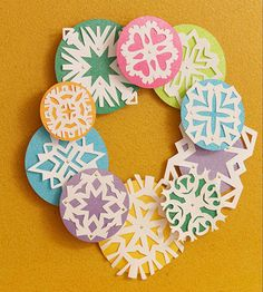 Turn leftover cardstock into a cheery snowflake Christmas wreath. Cut several circles from cardstock in two different sizes. Secure white paper snowflakes to the circles with brads. Hot-glue the larger circles onto a flat wreath form. To elevate the smaller circles, hot-glue bottle caps to the wreath, then glue the circles on top of them.