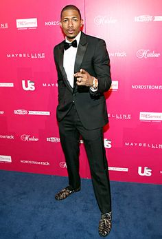 Nick Cannon in a suit, Giuseppe Zanotti shoes, a Jacob & Co. watch and socks from his own line.