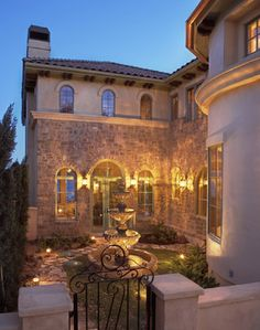 European - Tuscan Stone, flag stones, cozy lit up courtyard, 3-tiered fountain, wrought iron gate, french doors, arched windows