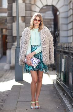 A Jil Sander paisley clutch and patterned skirt are complementary in similar hues.   - HarpersBAZAAR.com