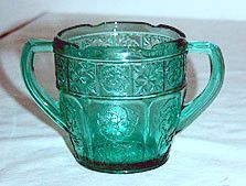 This is a Depression Glass children's sugar bowl in the Doric and Pansy pattern made by Jeannette. The color is ultramarine or teal and it is from the Pretty Polly children's dishes set. It stands 2.5