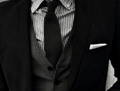 Outfit with grey and white striped shirt , black tie, dark grey vest, black suit coat and white handkerchief