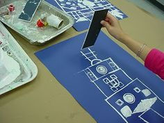 Blueprints created by using Legos, marker tops, cardboard scraps, sponge shapes and cardboard tubes were dipped in white paint and stamped on blue paper