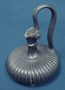 The other kind of Etruscan pottery was all black, often with molded decorations on it. We call this second kind of Etruscan pottery bucchero (BOO-ker-oh), from the Spanish word for a vase.