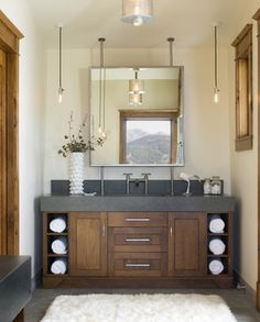 Eclectic Bath: solid counter/sink combo, drop pendant lights, industrial type faucet, slate tile floor, wood cabinet, unique mounted mirror frames space perfectly.