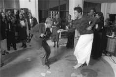 Writing legends Amiri Baraka and Maya Angelou dance in the atrium of the Schomburg Center for Research in Black Culture, over the interred ashes of Langston Hughes.