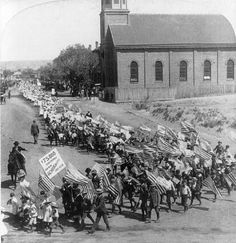 school children parading, carrying u.s. flags to welcome president mckinley during his visit to el paso in 1901.