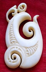Maori bone carving; notice the overall fish hook shape, and the three koru in the carved pattern.